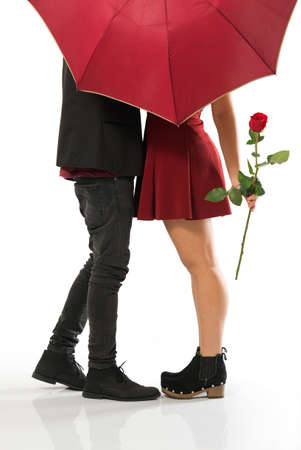 Young couple in love kissing behind red umbrella over white background
