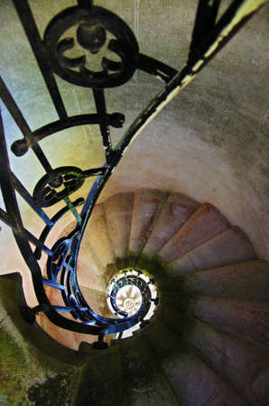 Spiral stone staircase with metallic rails  photo
