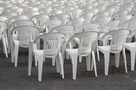 Rows of empty white chairs waiting for the audience