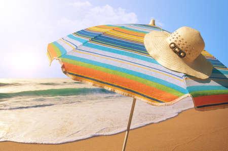 sunny day: Detalle de colorido parasol y sombrero de paja en la playa en un d�a soleado de verano