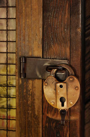 Old padlock on a wooden door with grid photo