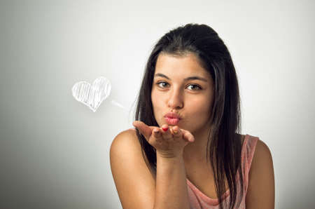 latina girl: Beautiful brunette teenager blowing a kiss Stock Photo