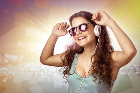Pretty young girl with headphones and sunglasses dancing and smiling over colorful  photo