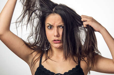Brunette teenager girl with anger expression pulling her messy hair Stock Photo