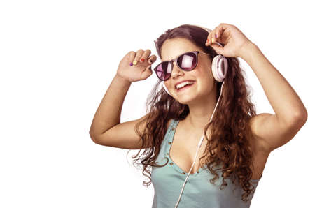 Pretty young girl with headphones and sunglasses dancing and smiling over white background photo