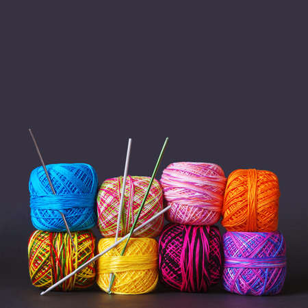 A stack of colorful yarn coils and needles over grey background photo