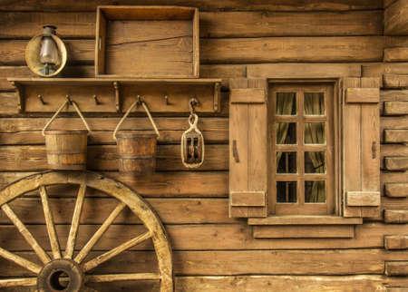 昔の木製ワイルドウェストの典型的な家の隣に荷馬車の車輪を詳細します。 写真素材