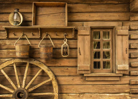Detail of old wagon wheel next to a wooden wild west typical house Archivio Fotografico