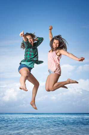 Two pretty teenager girls jumping of joy in the beach photo