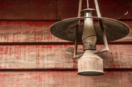 candil: Vieja lámpara de queroseno oxidada colgado en una pared de madera rústica
