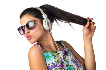 Pretty young girl with headphones and sunglasses dancing and holding her hair photo