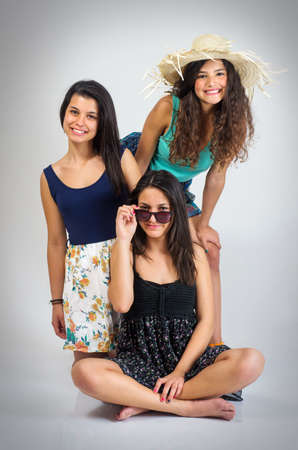 bff: Tree teenager girls best friends posing in the studio Stock Photo
