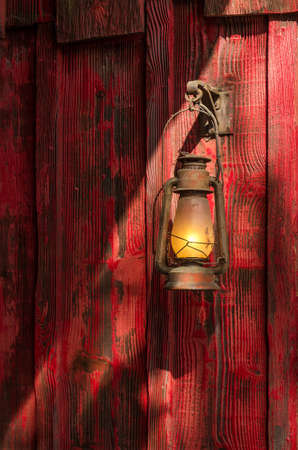 kerosene lamp: Old rusty kerosene lantern hanged on a rustic wooden wall
