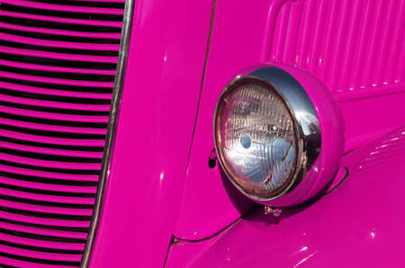 Closeup detail of the headlight of an antique car painted pink photo