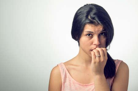nerveux: Portrait d'une jeune fille adolescente brune avec une expression nerveux et se ronger les ongles