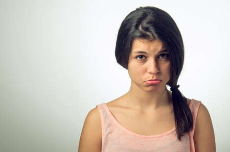 Portrait of a teenager brunette girl with pouting sad expression