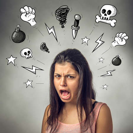 Angry teenager girl with furious expression screaming and swearing Stock Photo