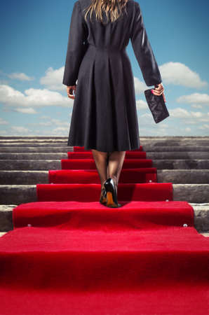 Elegant woman in black coat climbing a red carpet stairway photo