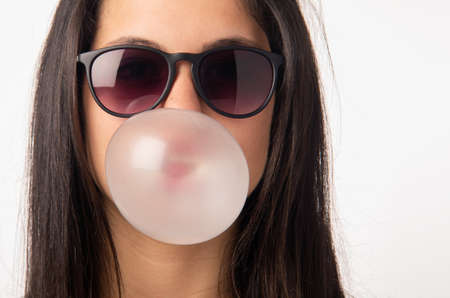 Brunette teenager girl with sunglasses blowing a bubble gum balloon Stock Photo