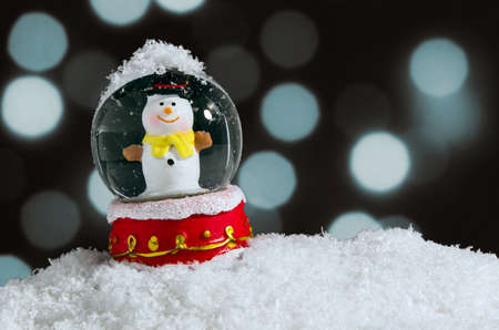 snow crystal: Snow globe with snowman over christmas lights background