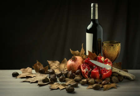 stilllife: Autumn Fall still-life with red wine, pomegranate and chestnuts