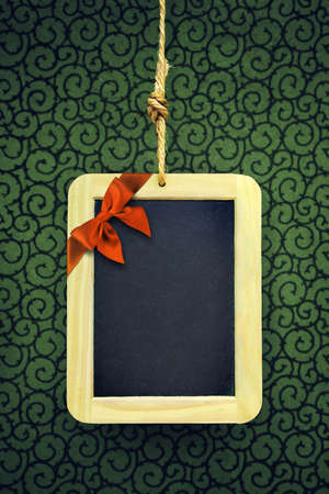 Hanged old slate board with Christmas bow in the corner photo