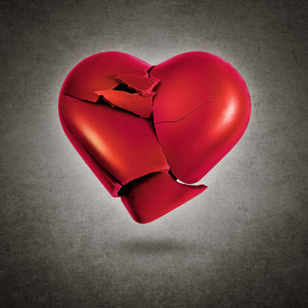 Broken red heart hovering over a gray textured background Stockfoto
