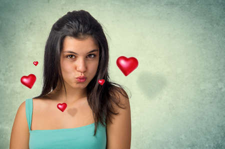 Beautiful brunette teenager expressing a kiss with hovering hearts photo