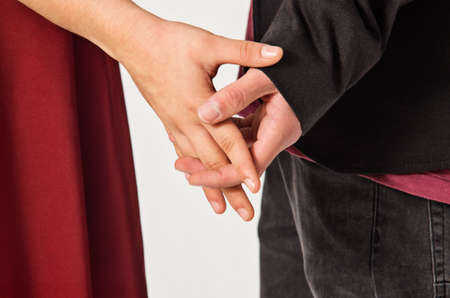interlaced: Detail of a loving couple holding hands with interlaced fingers