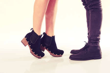 closeup on legs: Girlfriend standing on her toes to reach and kiss her boyfriend