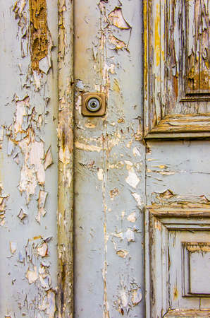 Detail of an old wooden door with peeling gray paint photo