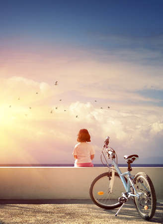 One bicycle and a little girl sitting on a wall watching the horizon