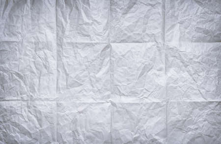 Bachground of folded and wrinkled old white paper sheet photo