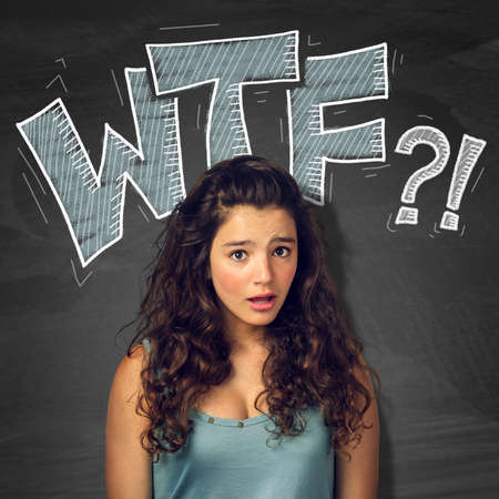 wtf: Pretty teenager girl with surprised expression over blackborad with signs Stock Photo