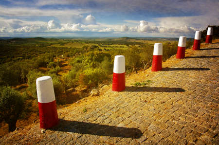 margin of safety: A row of red and white roadside pillars in a rural landscape Stock Photo