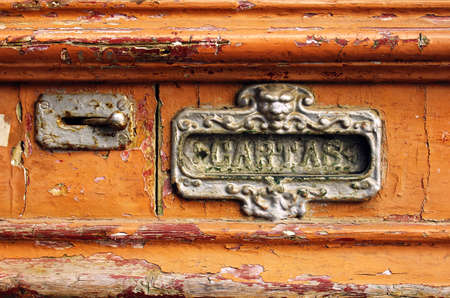 Old mailbox slot in an old wooden door painted orange photo