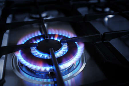 Closeup on gas stove burner with blue flames Stockfoto