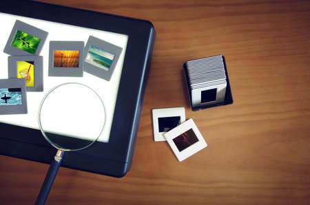 Top view of a light-box with color slides and a magnifier lens over a wooden table