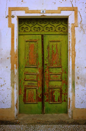 wretched: Damaged and peeling wooden door of an old rural house Stock Photo