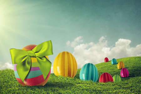 Colorful painted Easter eggs and green bow on a grass field