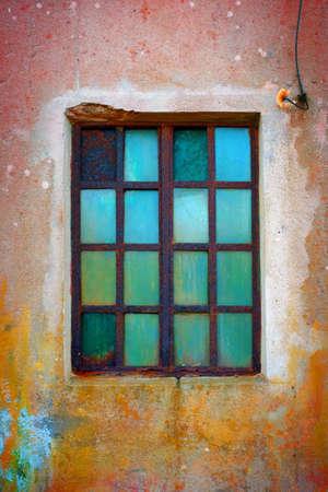 rejas de hierro: Ventana sucio con barras de hierro oxidado y vidrio verde viejo