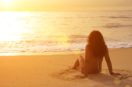 woman from behind: Young woman sitting in the sand looking at the sea at sunset