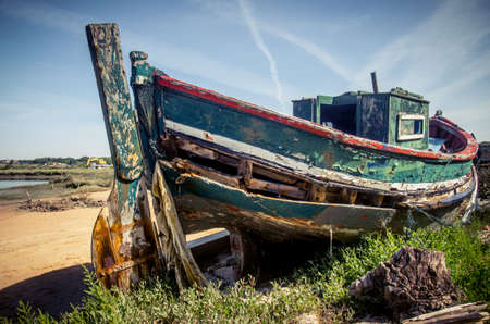 rotting: The remains of an old fishing boat rotting on the river shore Stock Photo