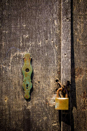 oxidized: Detail of a old scratched wooden door with rusty padlock Stock Photo