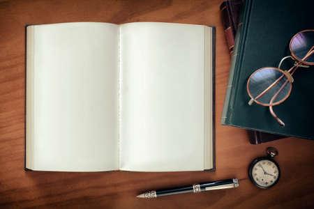libro abierto: Abra el cuaderno, una pluma y un reloj y un par de gafas en la parte superior de los libros