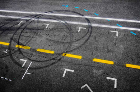 Top view of the asphalt of a car racing pit stop with painted signs and tire marks