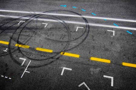 huellas de neumaticos: Vista superior del asfalto de una parada en boxes de carreras de coches con señales pintadas y marcas de neumáticos