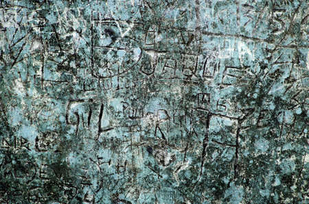 vandalize: Grunge background of graffiti and sayings carved on a blue wall Stock Photo