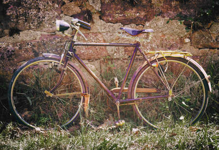 original bike: Old typical bicycle parked against a stone wall