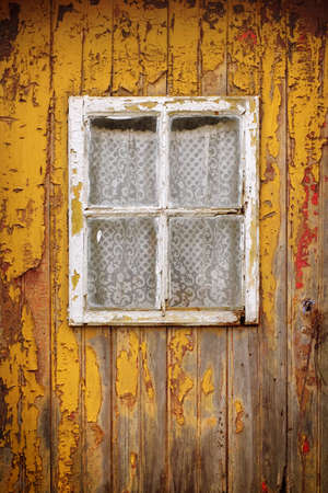 the desolate: Detail of a weathered yellow wooden door with a small window